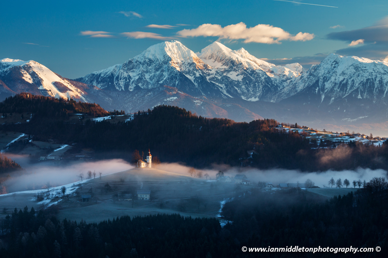 View from Rantovše hill across to Sveti Tomaz nad Praprotnim (church of Saint Thomas) with the Kamnik Alps behind in the Skofja Loka hills, Slovenia.