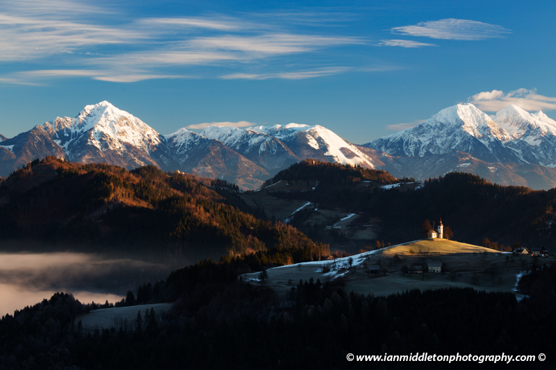 View from Rantovše hill across to Sveti Tomaz nad Praprotnim (church of Saint Thomas) with the Kamnik Alps behind in the Skofja Loka hills, Slovenia.