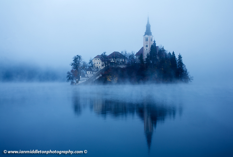 The famous Island church enshrouded in mist over Lake Bled.