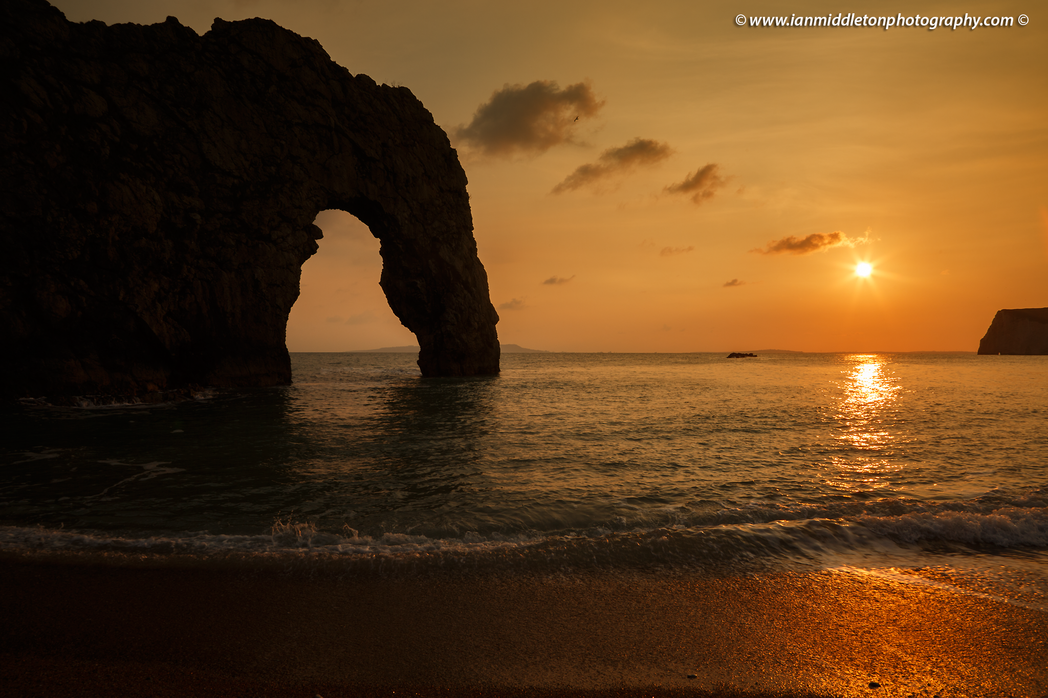 The late afternoon sun casts a warm glow over Durdle Door rock arch and beach at sunset, Dorset, England.