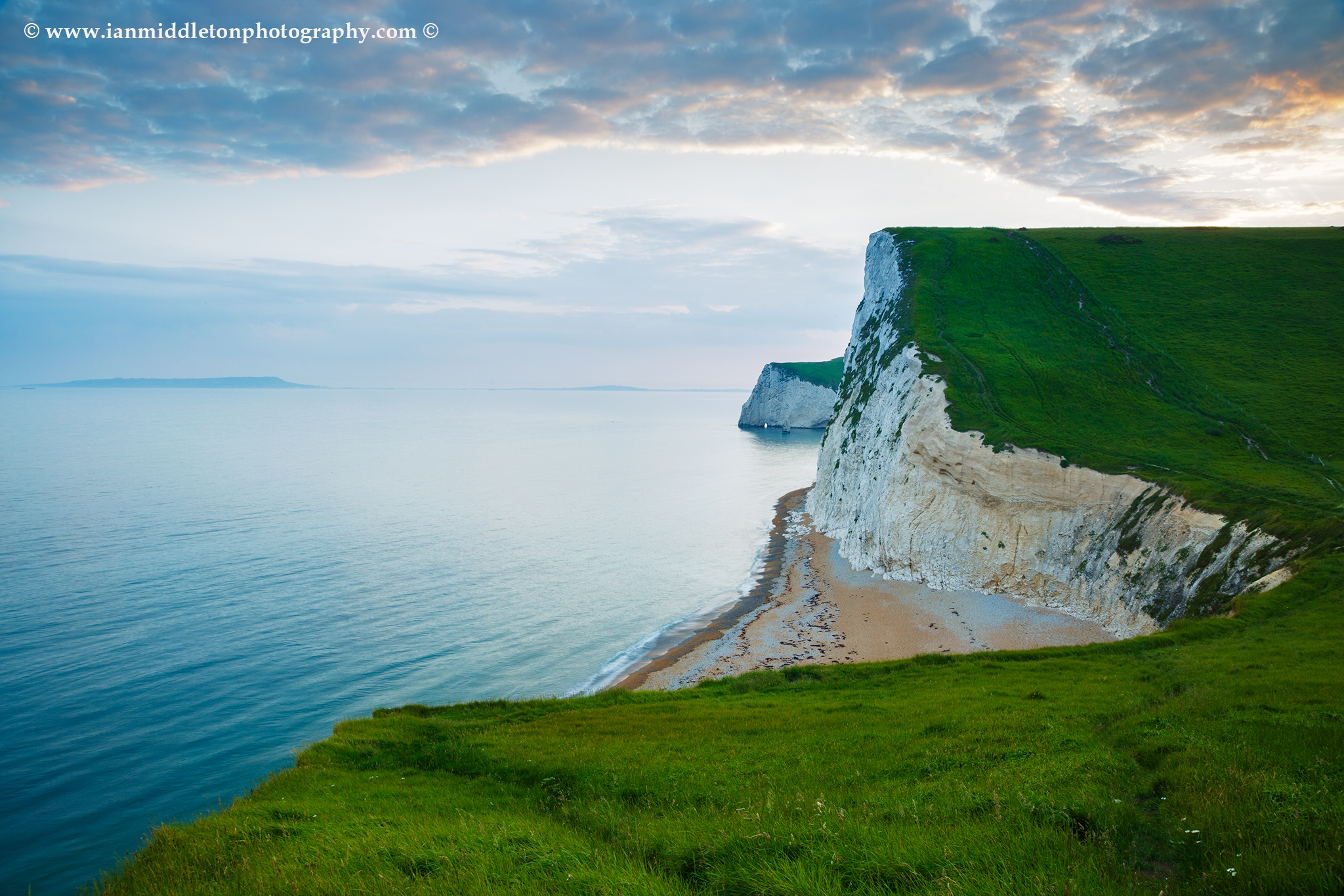 View across the cliffs to Bats Head from the cliffs above Durdle Door beach as the sun goes down for the evening, Dorset, England. Durdle door is one of the many stunning locations to visit on the Jurassic coast in southern England.