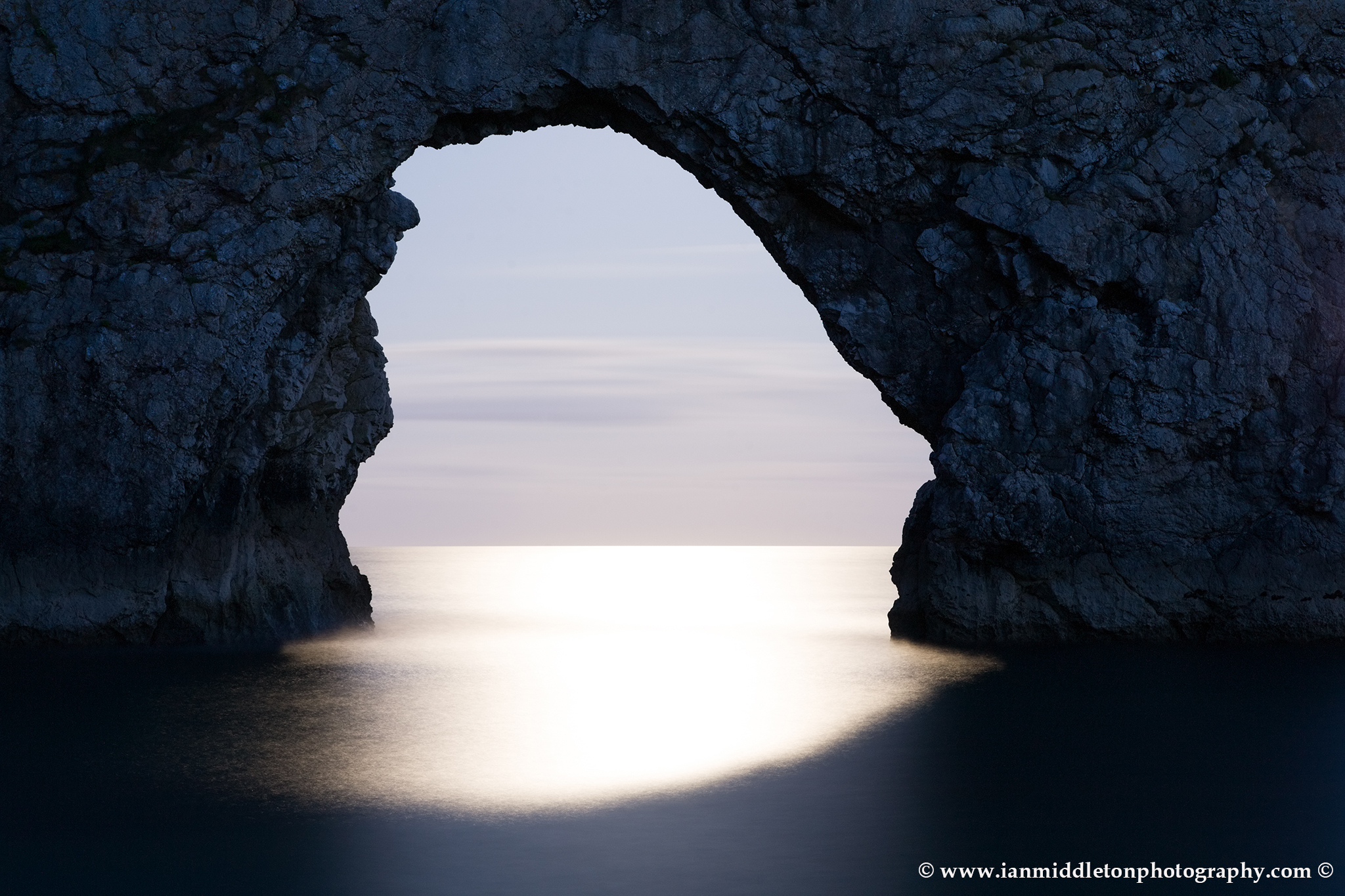 Durdle Door in the moonlight, Dorset, England. Captured late evening as the moonlight flooded through the rock's archway. Durdle door is one of the many stunning locations to visit on the Jurassic coast in southern England.