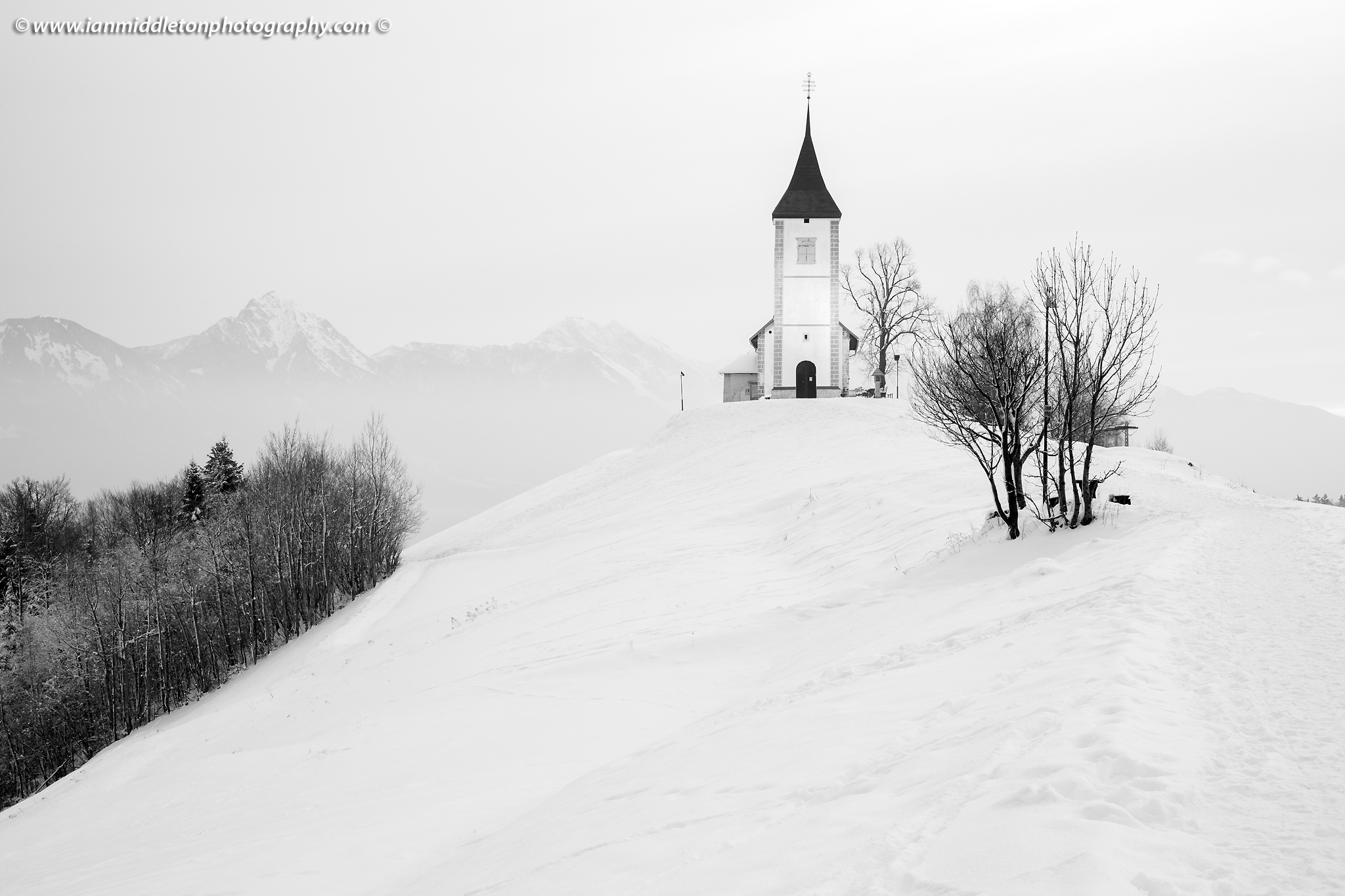 Jamnik church of Saints Primus and Felician in winter, perched on a hill on the Jelovica Plateau with the kamnik alps and Storzic mountain in the background, Slovenia.