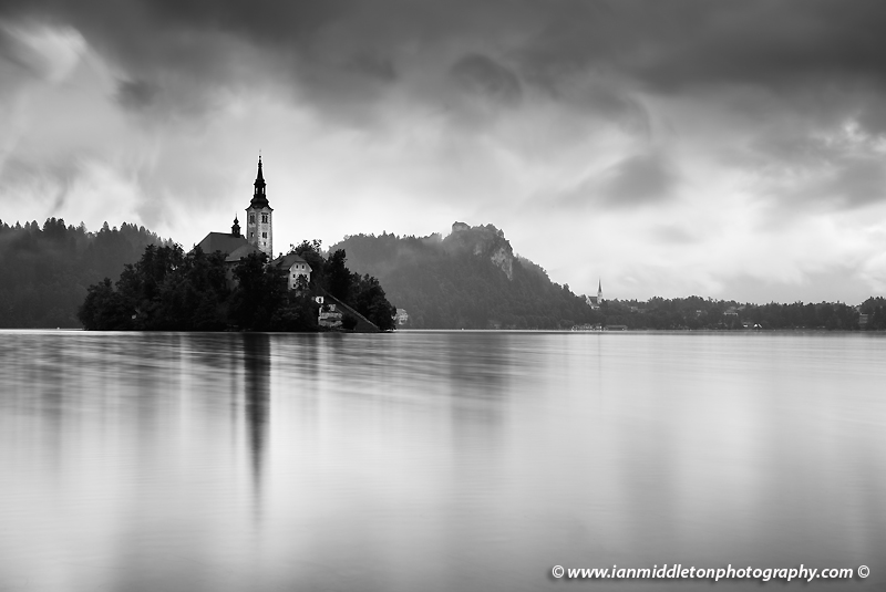 Morning at Lake Bled's island church of the assumption of saint mary and hilltop castle after a night of heavy summer rain, Slovenia.
