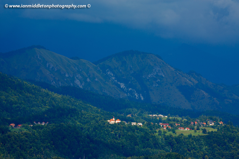 The small village of Šenturška Gora spot lit as a summer storm passes over. The village sits in the footihills of the Kamnik Alps, Gorenjska Slovenia. The photo was taken from Brnik, near the airport.