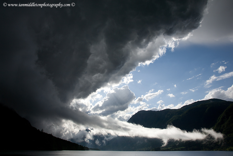 Stormy weather and beautiful light and clouds scattering over Bohinj Lake after a massive storm blew over the Bohinj valley, Triglav National Park, Slovenia.