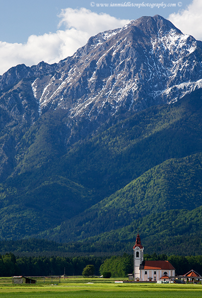 View of the the church of saint John in the shadow of Storzic mountain, Brnik, near the Ljubljana airport, Slovenia. At 2132m Storzic is the highest peak in the Kamnik Alps mountain range.