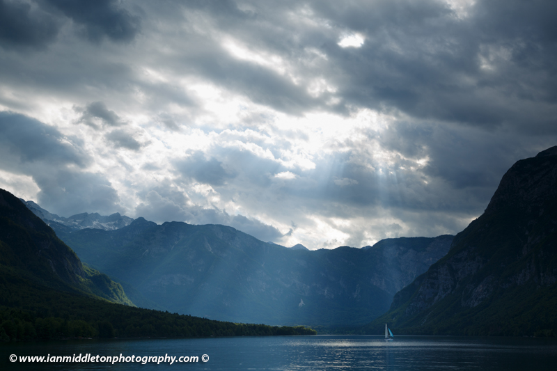 A lone sailing boat as light breaks over the mountains beside Lake Bohinj, Triglav National Park, Slovenia.