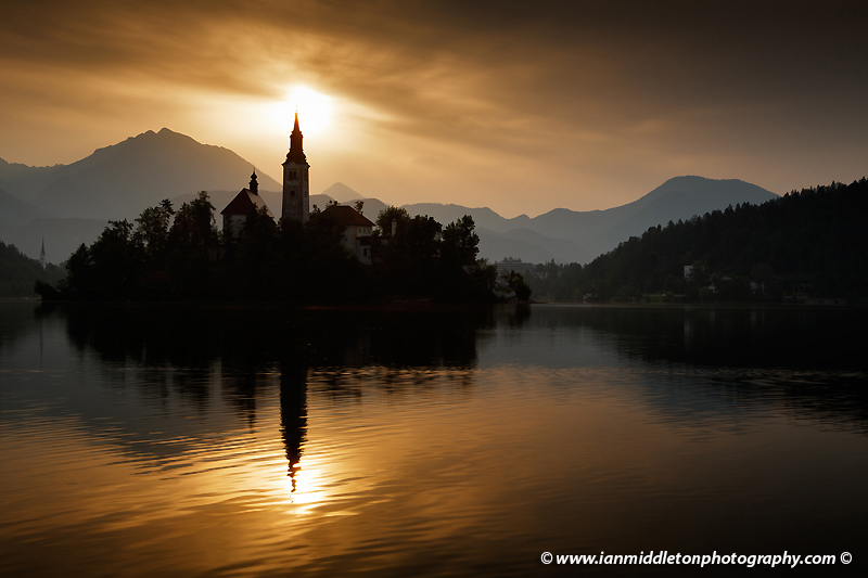 View across the beautiful Lake Bled, island church and hilltop castle at sunrise with the beautiful Karawanke mountains in the background, Slovenia. Lake Bled is Slovenia's most popular tourist destination and the Karawanke mountains form the border between Slovenia and Austria.