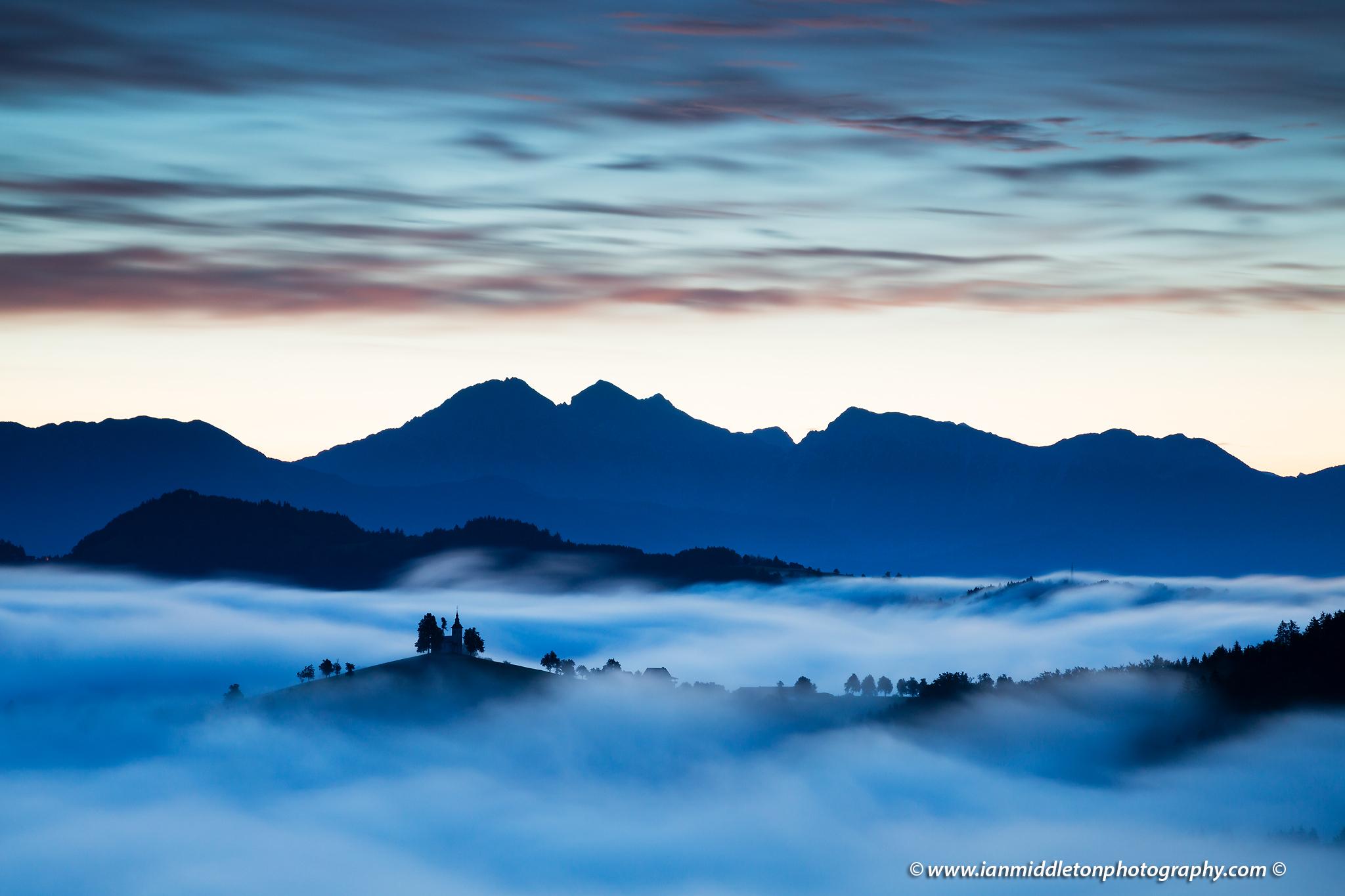 View at dawn from Rantovše hill across to Sveti Tomaz nad Praprotnim (church of Saint Thomas) and the Kamnik Alps, Slovenia.