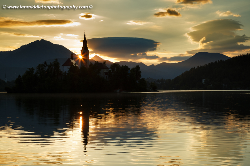 Sun rising over Lake Bled and the island church of the assumption of Mary with the Karavanke mountains in the background, Slovenia.
