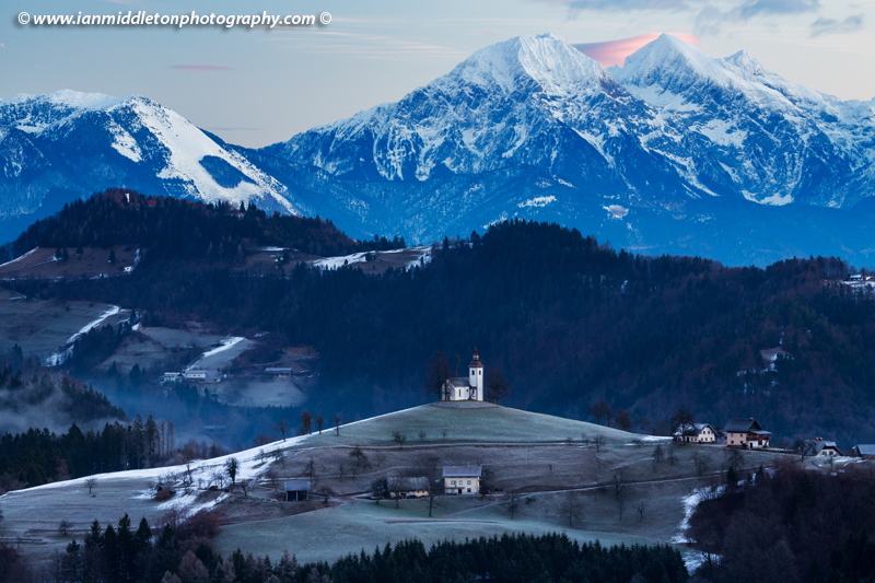 View at sunrise in winter from Rantovše hill across to Sveti Tomaz nad Praprotnim (church of Saint Thomas) and the Kamnik Alps, Slovenia.