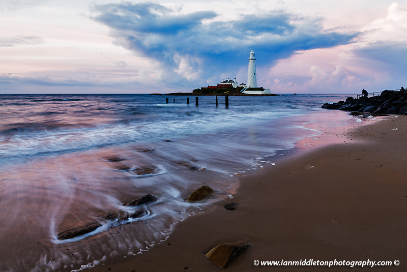 Saint Mary's Lighthouse on Saint Mary's Island, situated north of Whitley Bay, Tyne and Wear, North East England. Seen at sunset from the beach beside the causeway that runs out to the island. Whitley Bay is situated just north of Newcastle.