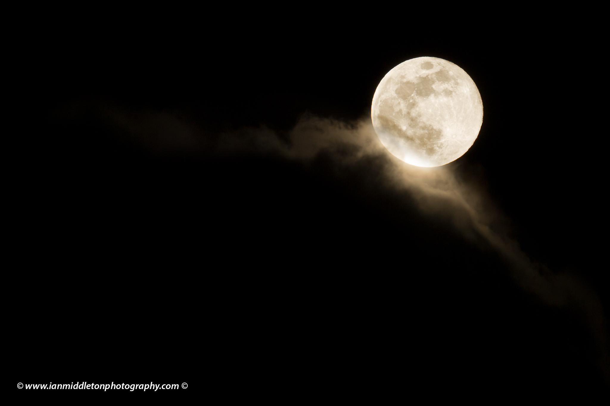 Easter blue moon of March 2018 rising out of the clouds after a rainstorm