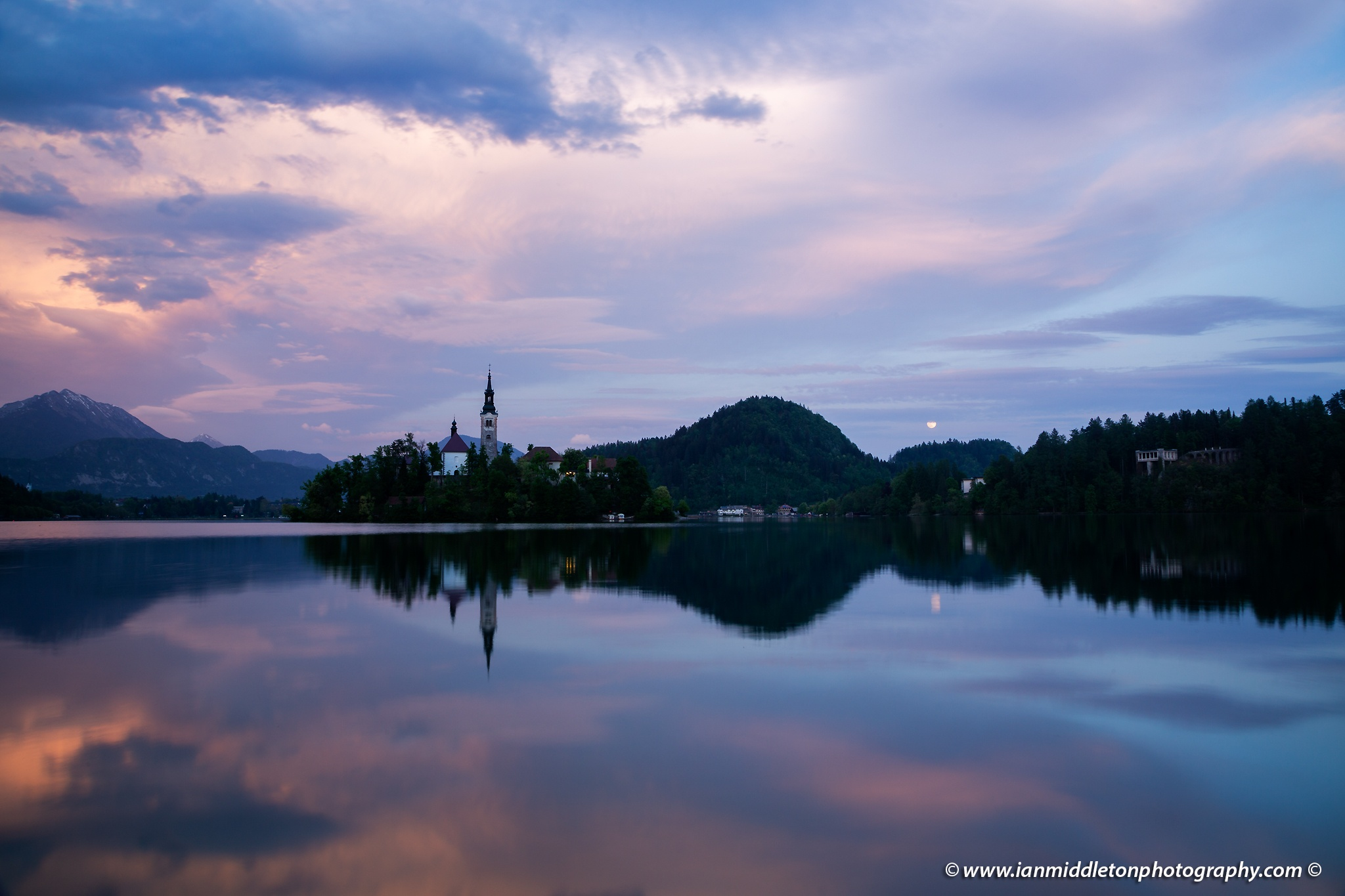 Lake Bled at sunset with the moon rising above the nearby hills, Slovenia .
