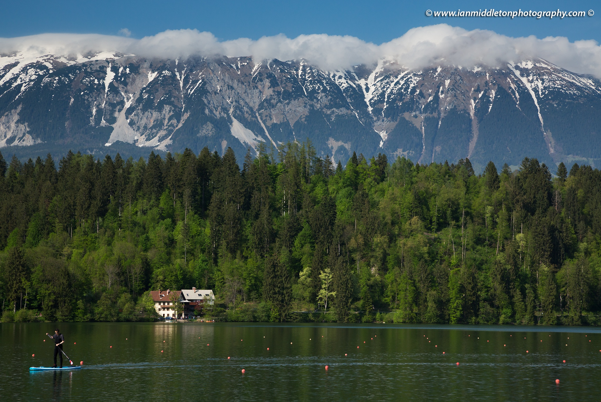 Man standup paddleboarding (SUP) on Lake Bled, Slovenia with the Karavanke Mountains in the background.