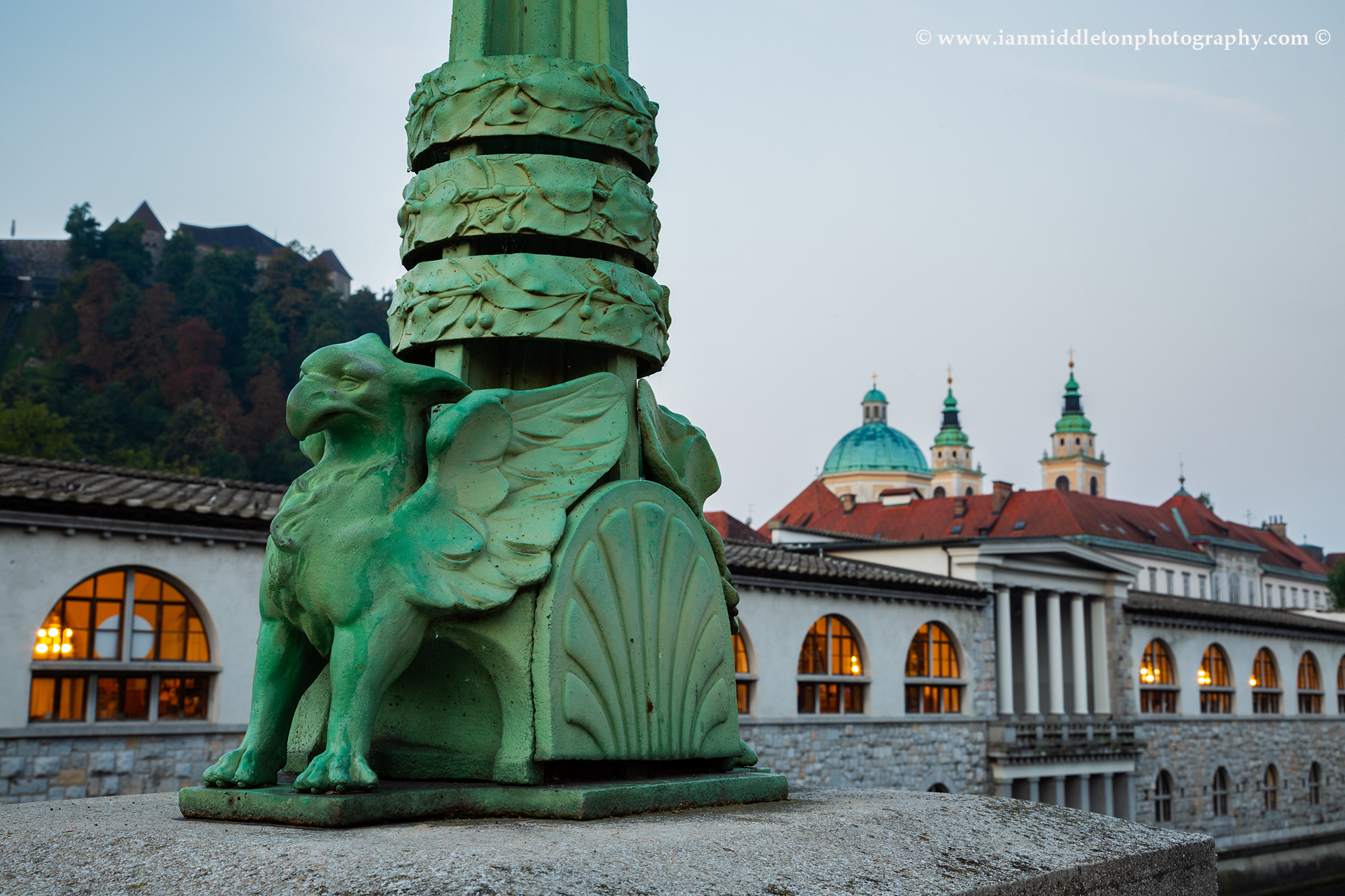 Ljubljana Dragon Bridge Griffin with castle, marketplace and cathedral of Saint Nicholas in the background, Slovenia.