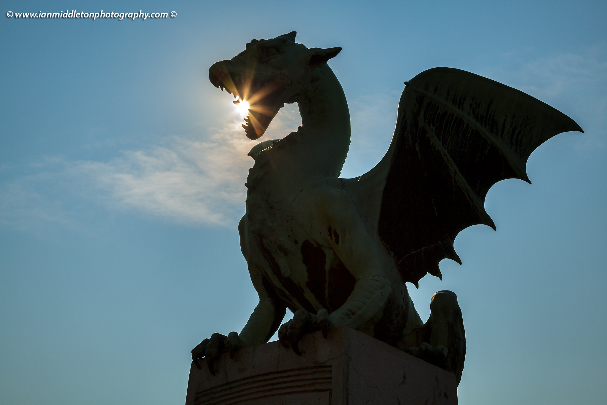 Sunburst through the mouth of a dragon on the Dragon Bridge in Ljubljana, Slovenia.