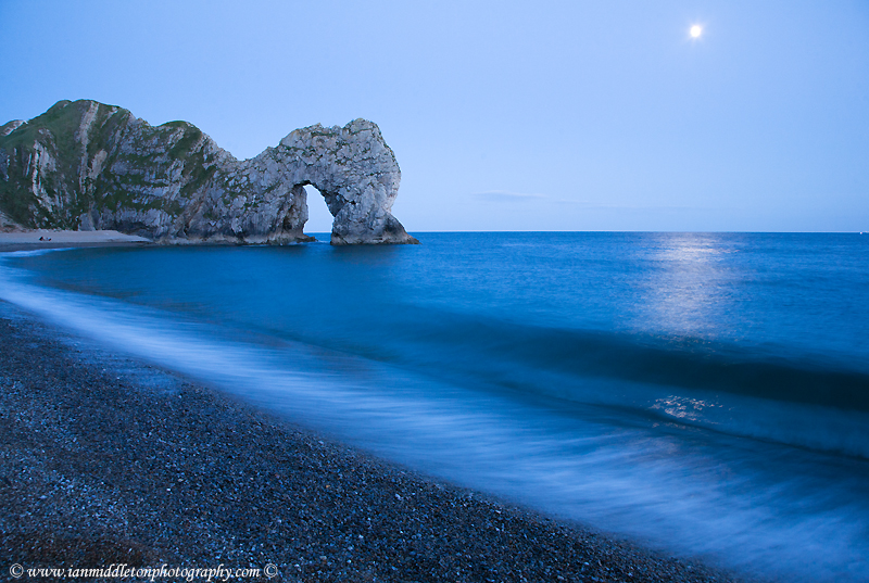 Durdle Door and beach in the moonlight, Dorset, England. Captured late evening as the moonlight flooded across the sea. Durdle door is one of the many stunning locations to visit on the Jurassic coast in southern England.