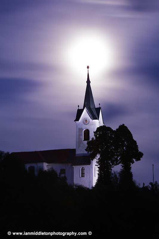 The 2013 supermoon rises over the spire of the church of Saint Marjeta (Sveta Marjeta) in Prezganje in the Jance hills to the east of Ljubljana, Slovenia. This was shot on the evening of June 22nd, the night before totality and the moon was approximately 98% full.