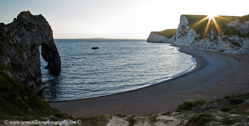 Durdle Door beach as the sun disappears over the cliffs, Dorset, England. Durdle door is one of the many stunning locations to visit on the Jurassic coast in southern England.