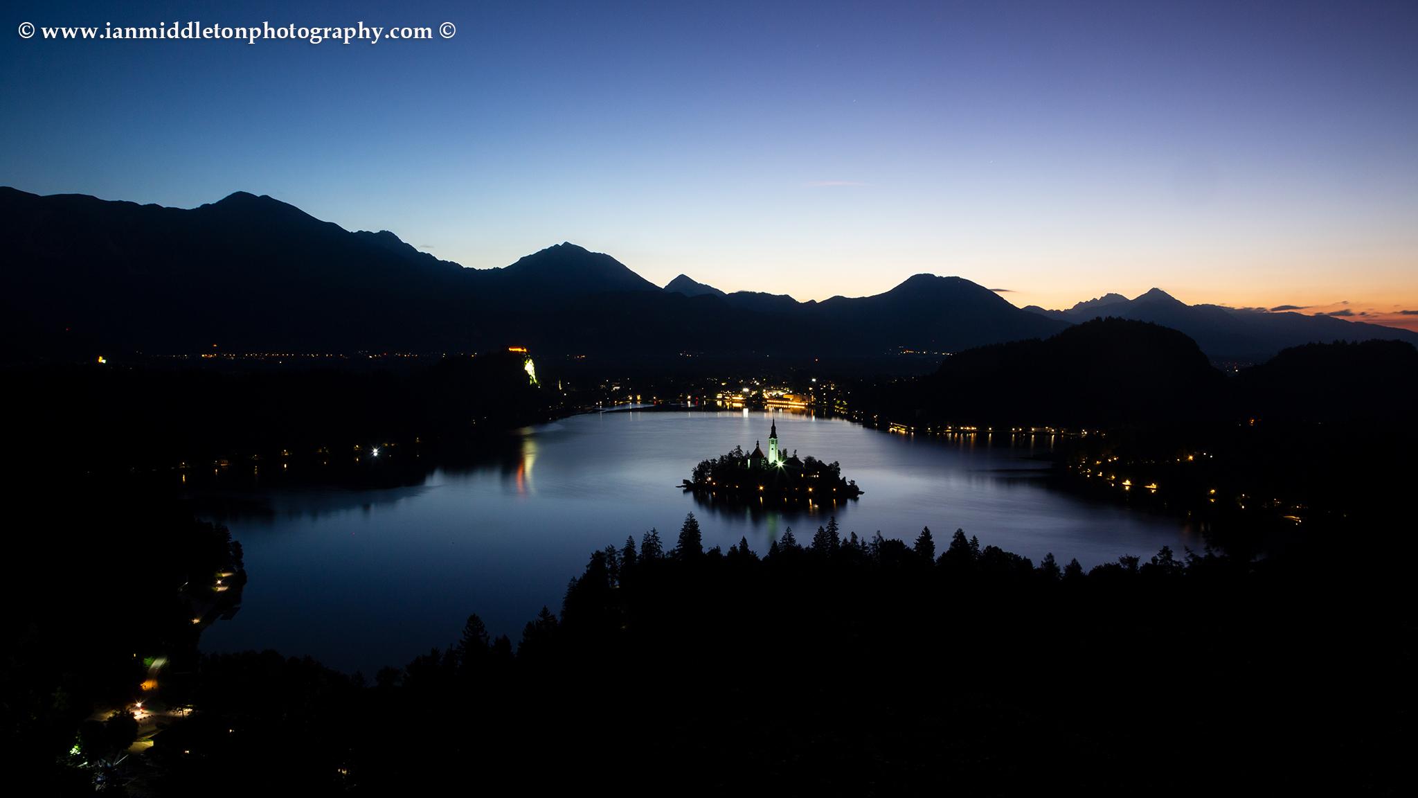 View across Lake Bled to the island church and clifftop castle from Ojstrica at dawn, Slovenia.