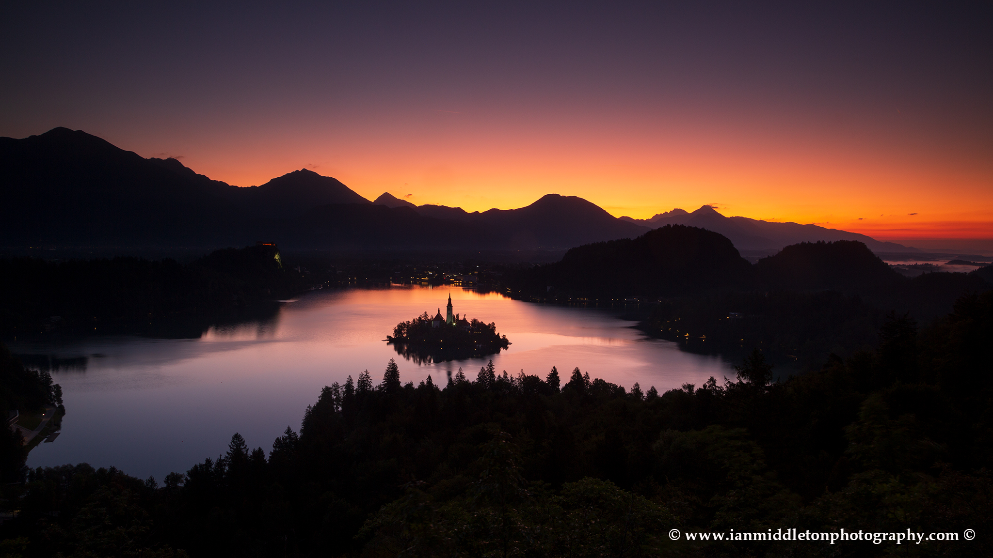 Sunrise from the viewpoint of Lake Bled to the island church and clifftop castle from Ojstrica, Slovenia. Here you can see the Karavank Alps and the Kamnik Alps