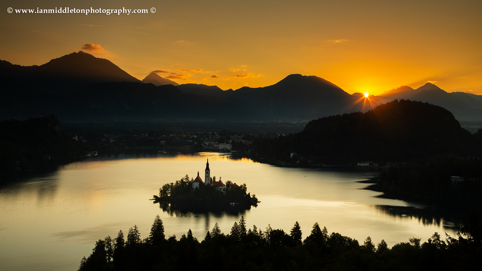 Sunrise view across Lake Bled to the island church and clifftop castle from Ojstrica as the run rises beside Storzic and Kocna mountains, Slovenia.