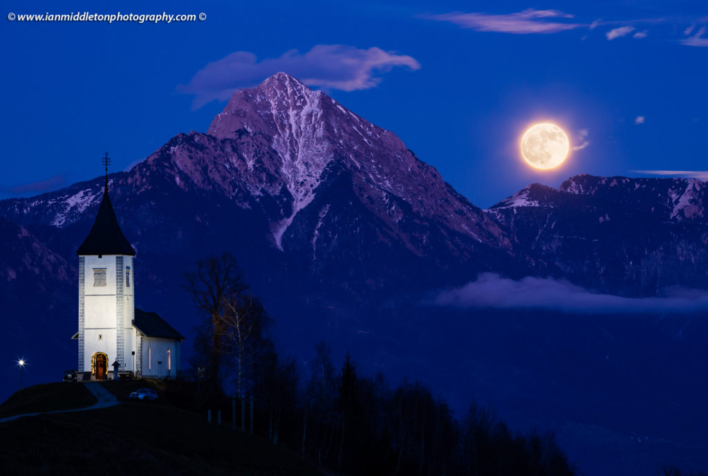 Full moon rising during the Blue Hourover Jamnik church of Saints Primus and Felician, perched on a hill on the Jelovica Plateau with the kamnik alps and Storzic mountain in the background, Slovenia.