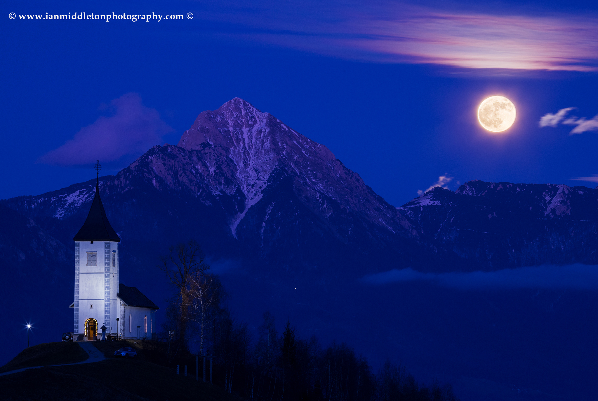 Full moon rising during the Blue Hour over Jamnik church of Saints Primus and Felician, perched on a hill on the Jelovica Plateau with the kamnik alps and Storzic mountain in the background, Slovenia.