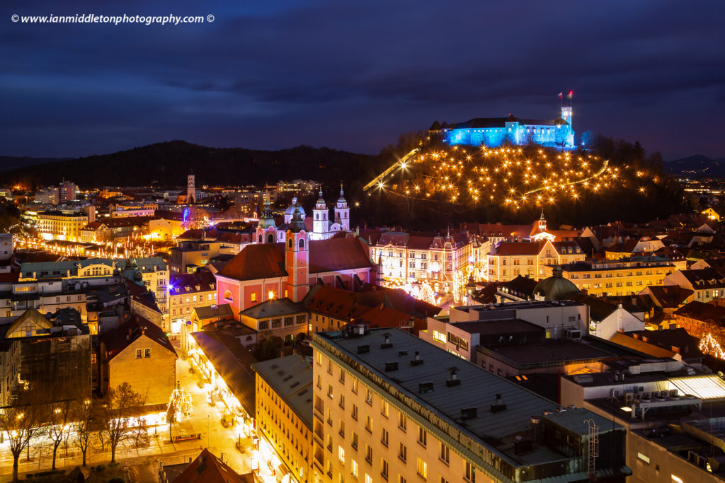 Christmas lights in Preseren Square with the franciscan church and castle on hill in Ljubljana, Slovenia. Seen from Neboticnik the Ljubljana castle, beautiful Franciscan church and christmas lights are beautiful sight every Christmas.
