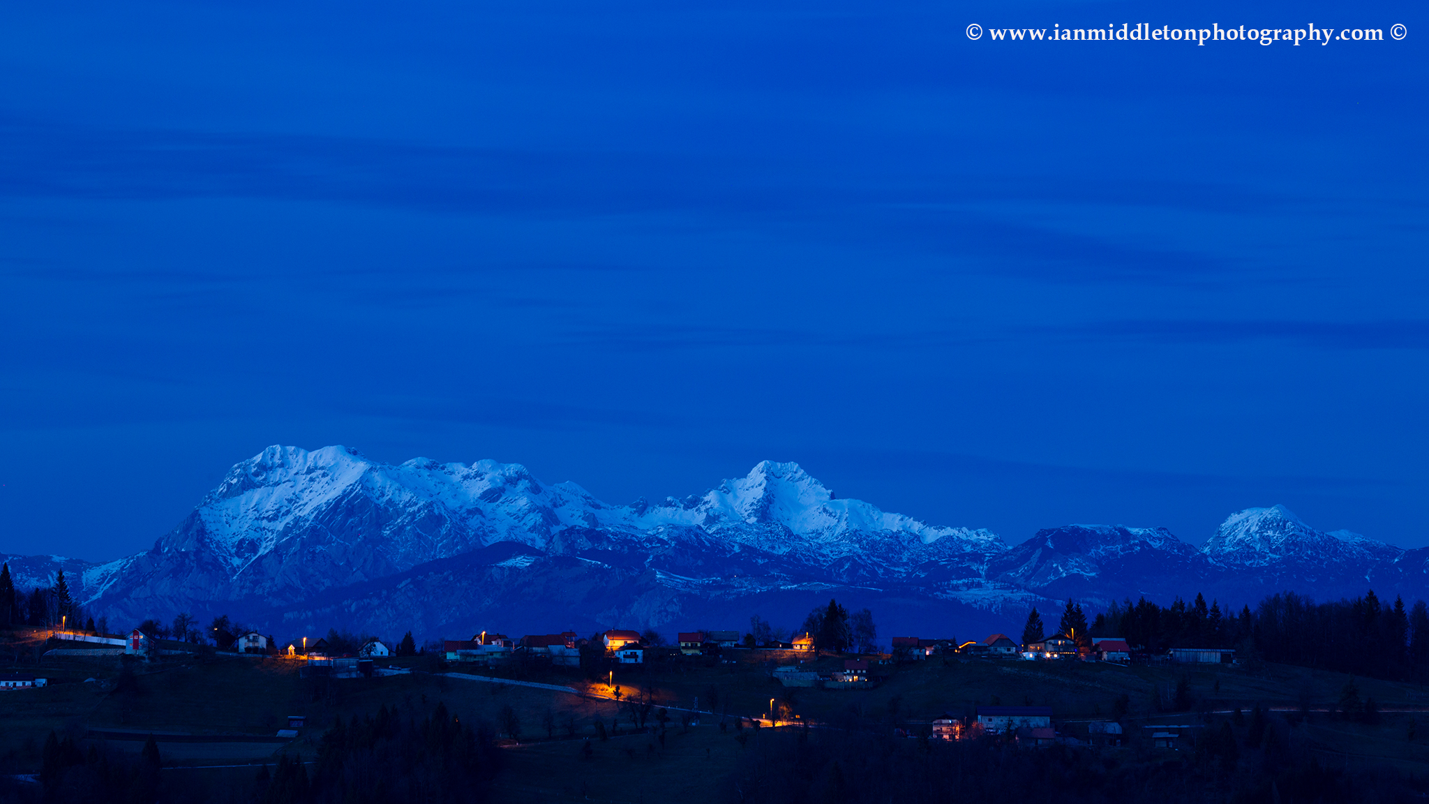 View across to the Kamnik Alps at dusk, seen from a hill in prezganje in the Jance hills to the east of Ljubljana, Slovenia