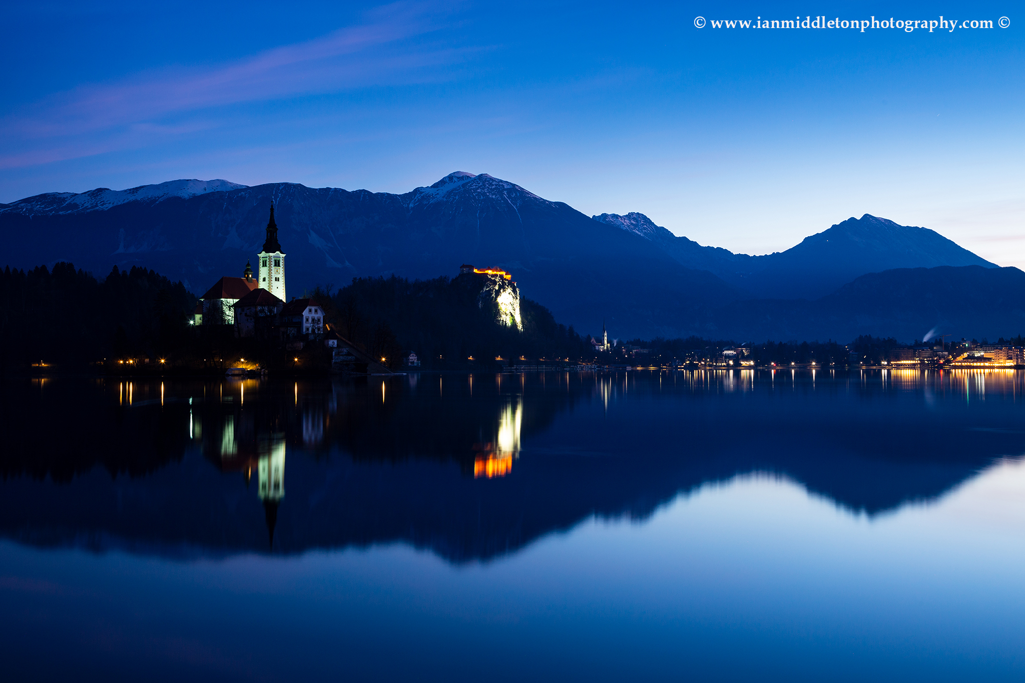 Dawn view across the beautiful Lake Bled, island church of the assumption of Mary, and hilltop castle, Slovenia.