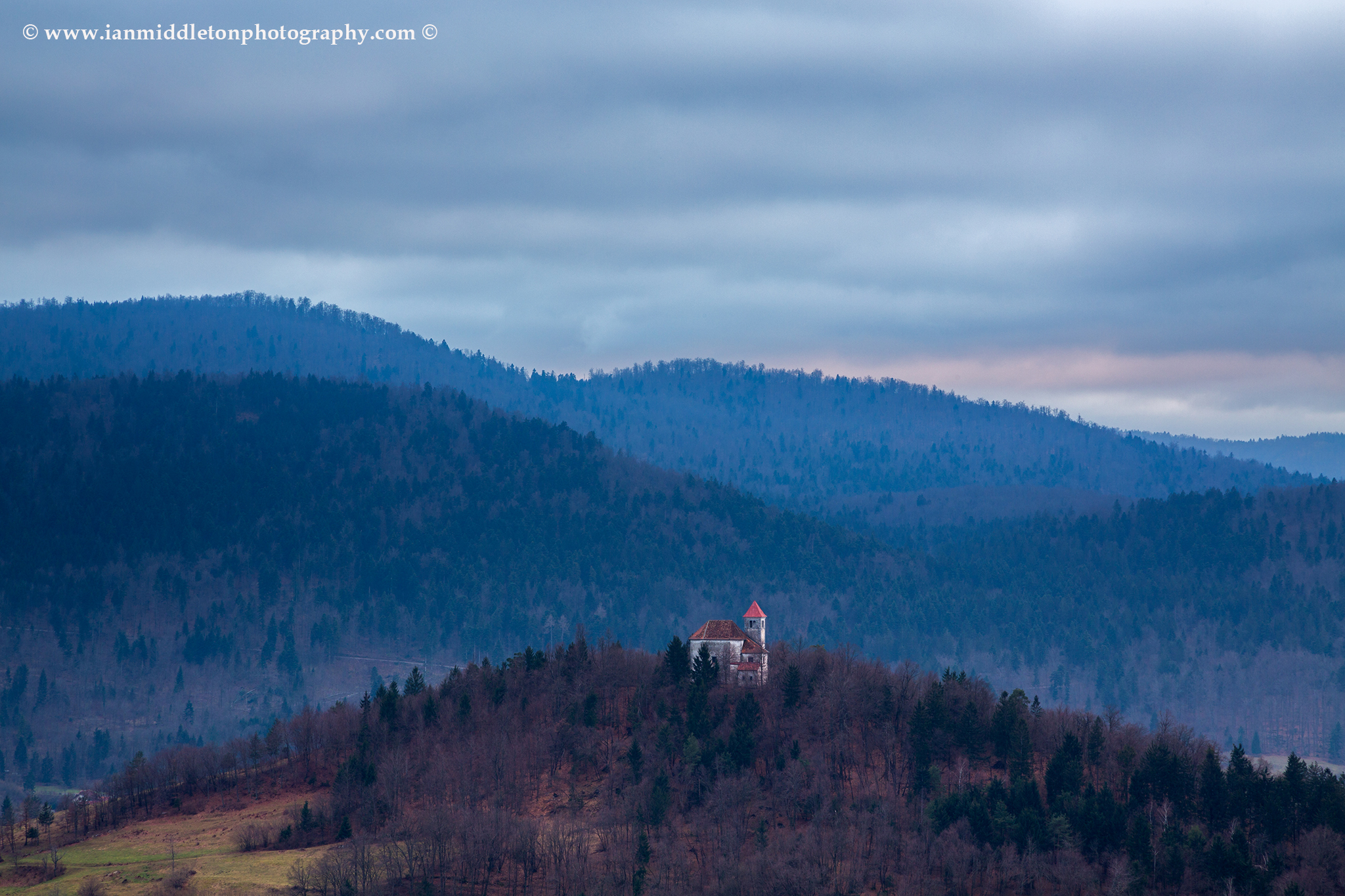 The church of Sveti Josef (Saint Joseph), Slovenia. Seen from the church of Saint Anna (Sveta Ana). Sveta Ana is perched upon an exposed hill overlooking the Ljubljansko Barje (Ljubljana moors) near the village of Preserje.