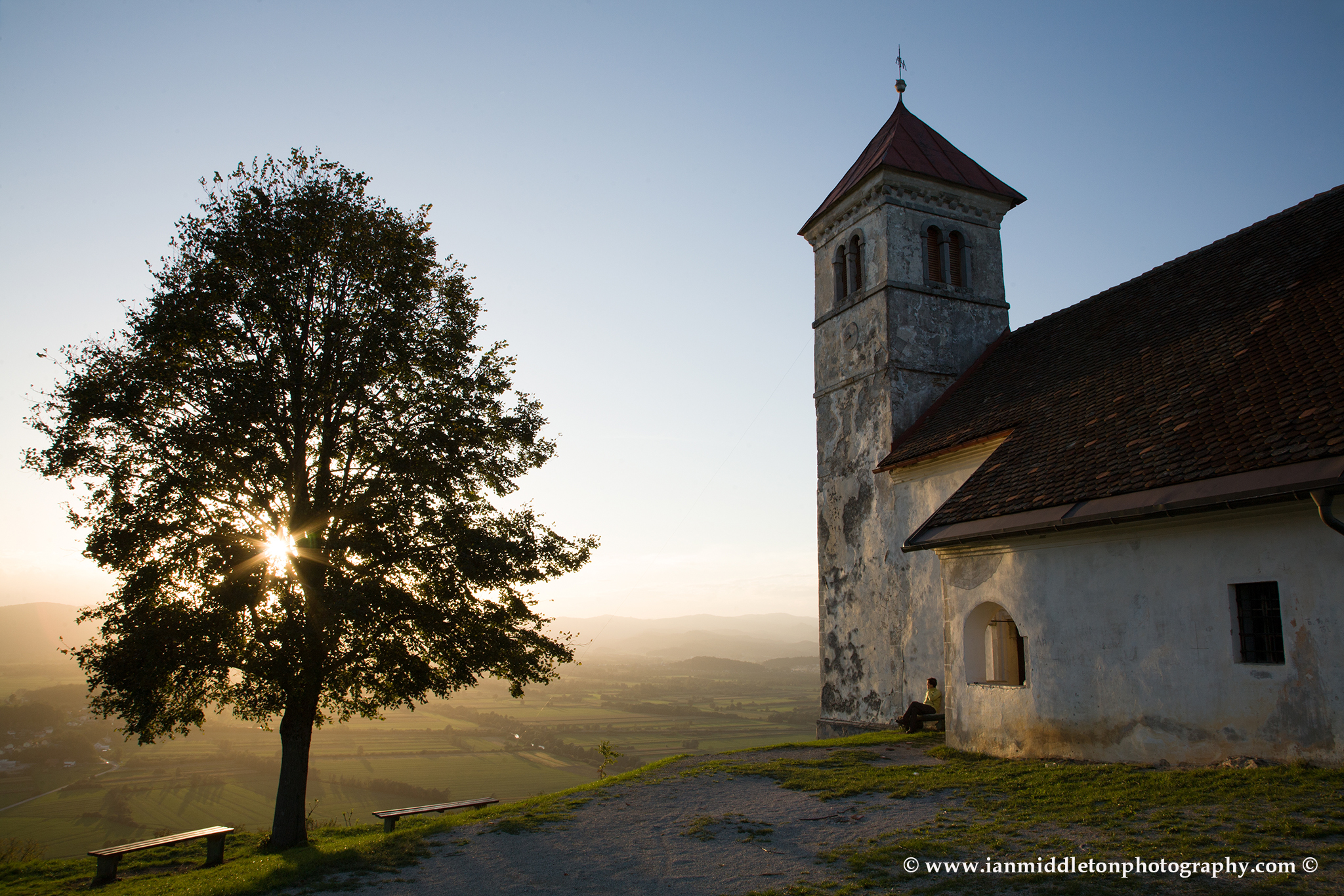 Soft light falls over the church of Saint Anna (Sveta Ana) as the sun falls down behind a nearby tree causing a sunburst through the leaves and branches. Sveta Ana is perched upon an exposed hill overlooking the Ljubljansko Barje (Ljubljana marsh) near the village of Preserje. The views from this hill are spectacular and many locals seem to come here for the evening.