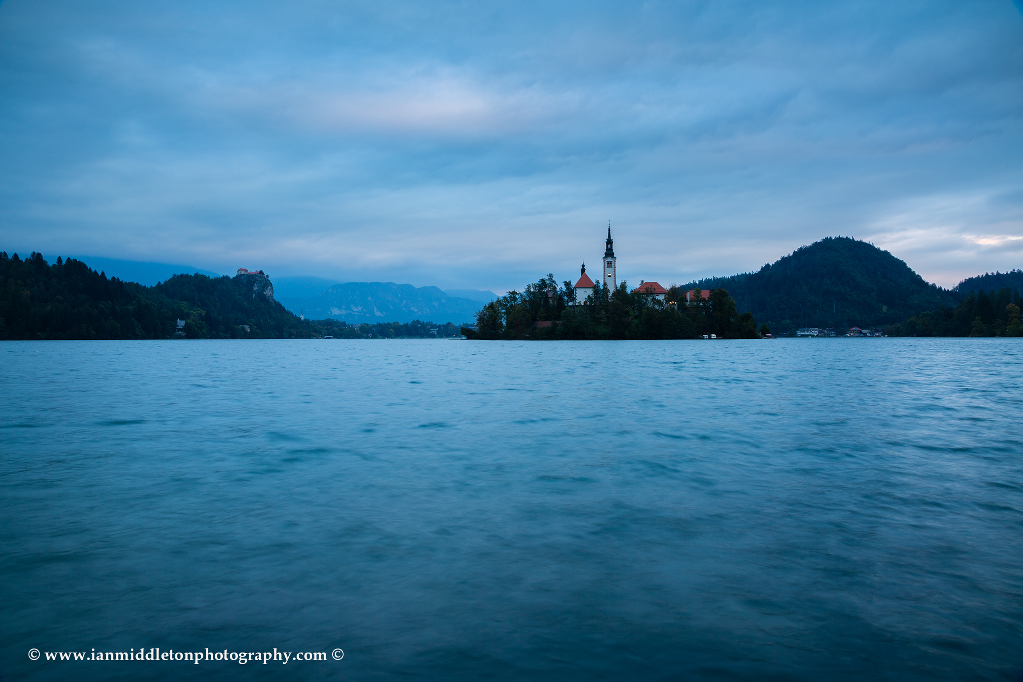 View across the beautiful Lake Bled, island church and hilltop castle at dusk, Slovenia.
