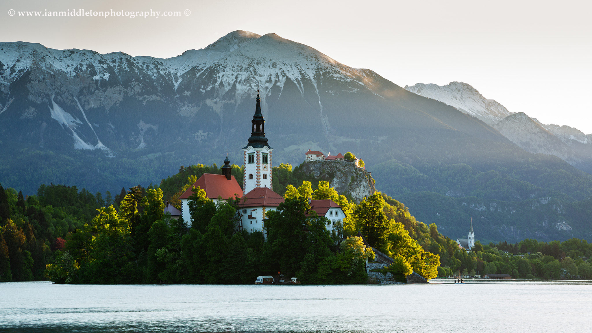 Morning spring light at Lake Bled's island church with the hilltop castle and Mount Stol of the Karavanke Mountains behind, Slovenia.