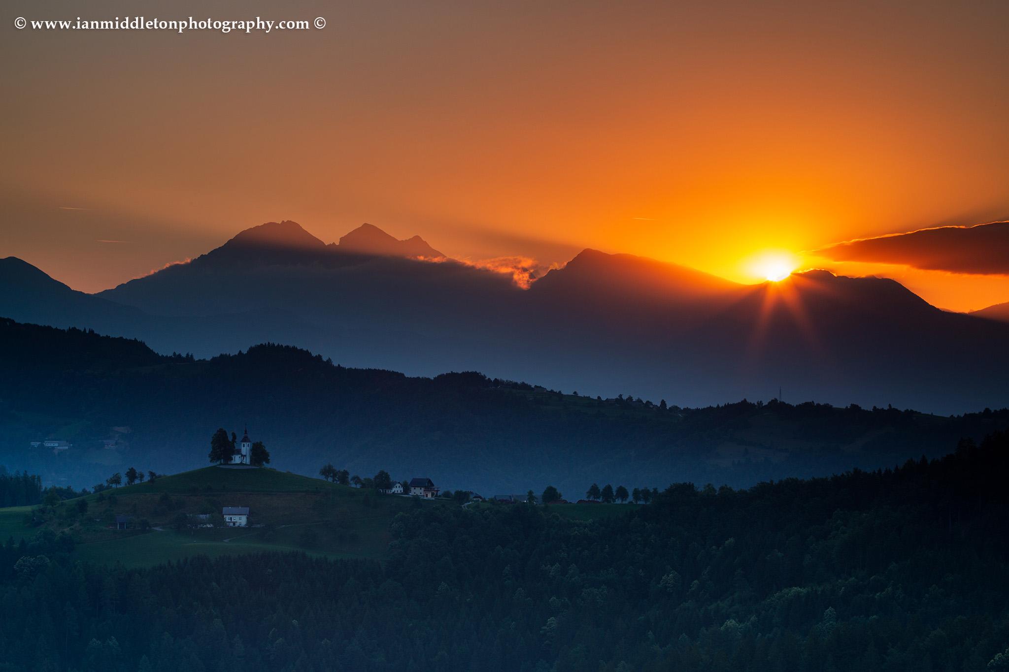 View at sunrise from Rantovše hill across to Sveti Tomaz nad Praprotnim (church of Saint Thomas) and the Kamnik Alps, Slovenia.