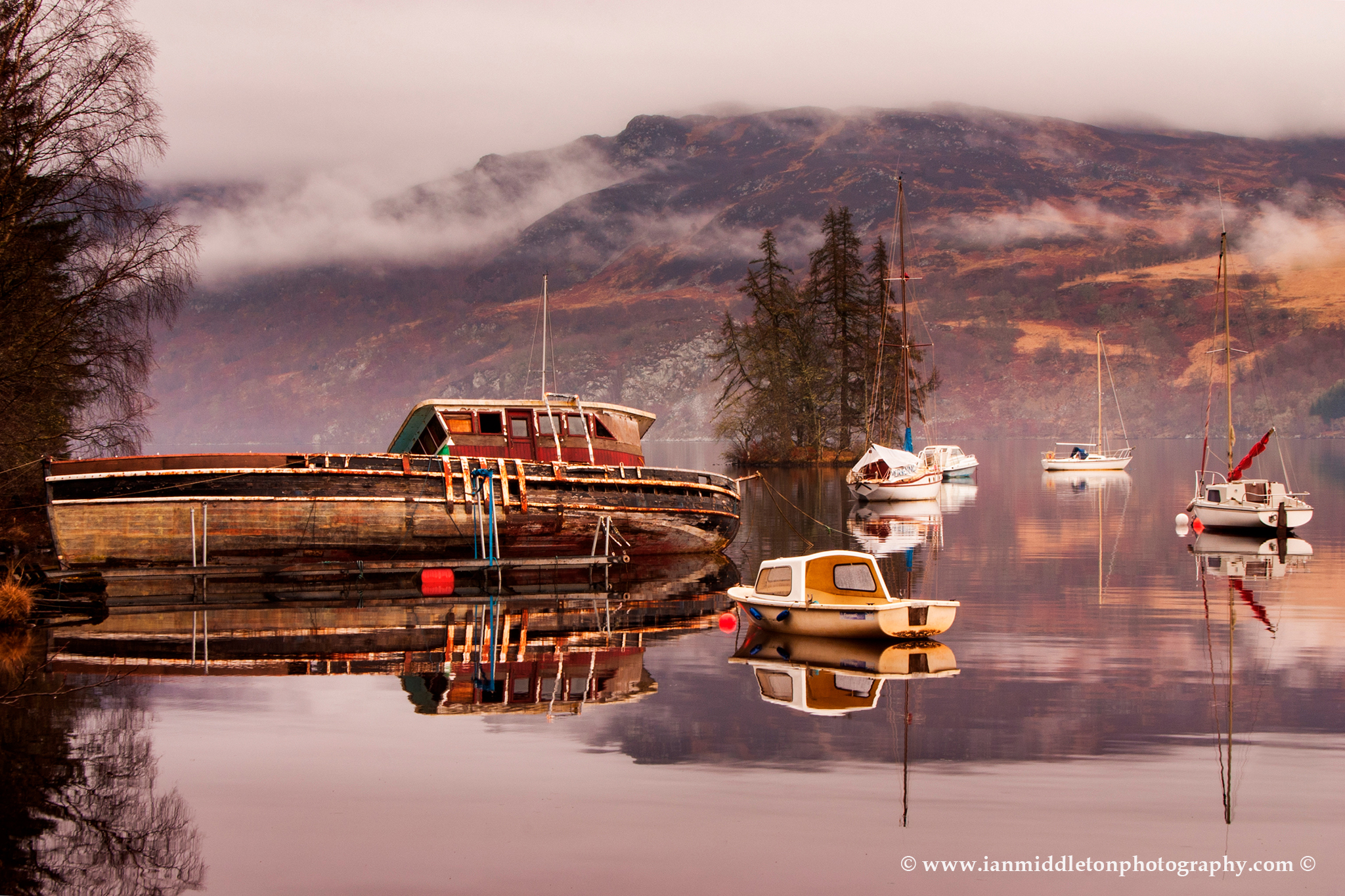 Misty morning reflections of Loch Ness in Scotland. Boats reflected as the morning mist dissipates near Fort Augustus.