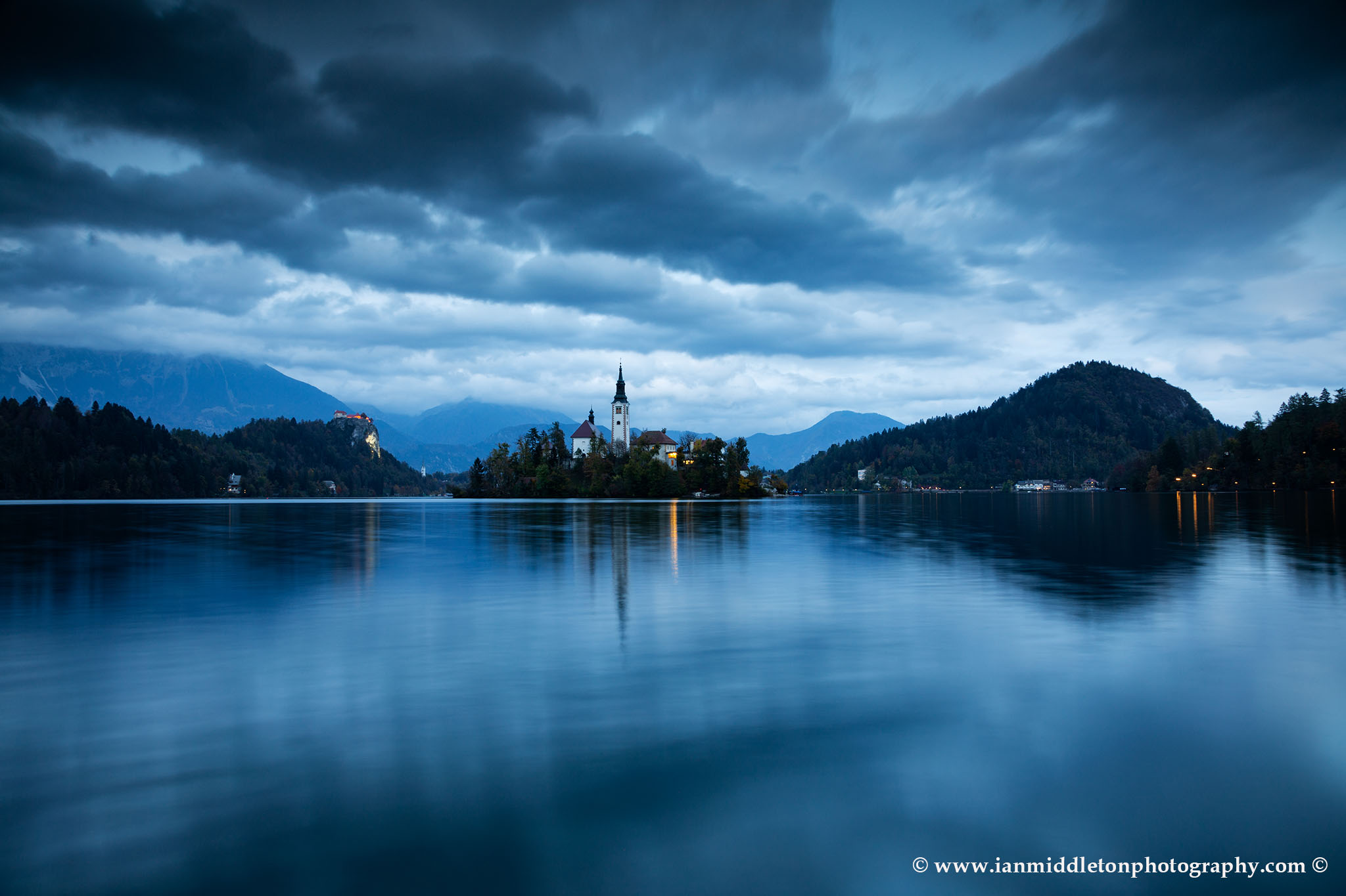 View across the beautiful Lake Bled, island church and hilltop castle at dusk with the beautiful Karavanke mountains in the background, Slovenia. Lake Bled is Slovenia's most popular tourist destination and the Karavanke mountains form the border between Slovenia and Austria.