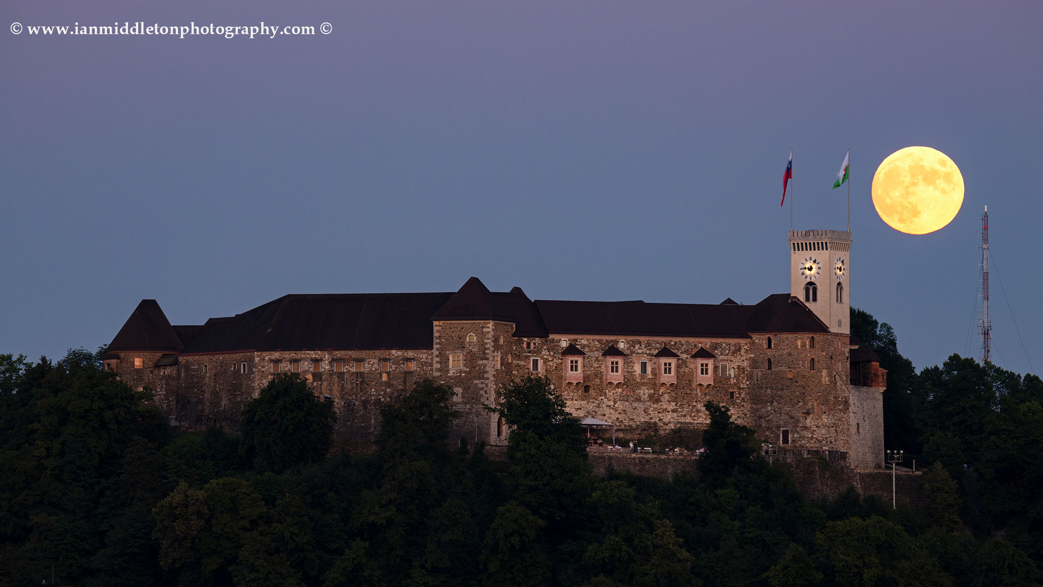 View across the to Ljubljana Castle as the full moon rises behind the tower. Seen from Tivoli Park, Ljubljana, Slovenia.