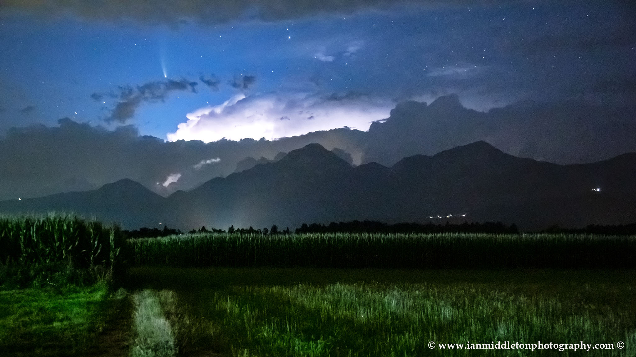 View of Neowise over the kamnik Alps with Storzic mountain to the right. Captured just as a flash of lightning lit up the clouds right over the mountains.