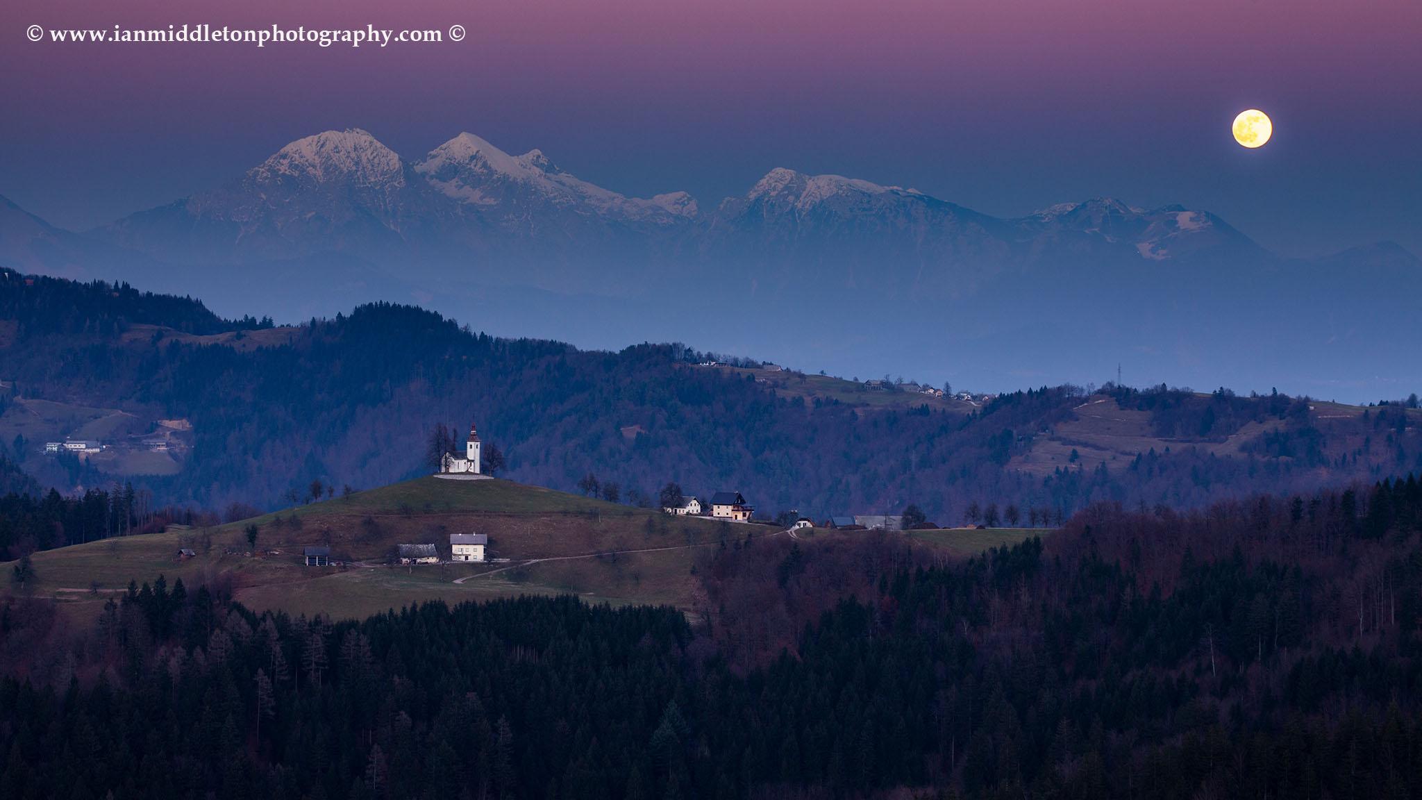 The full moon rising in winter over the mountains behind Sveti Tomaz nad Praprotnim (church of Saint Thomas) and the Kamnik Alps, Slovenia.