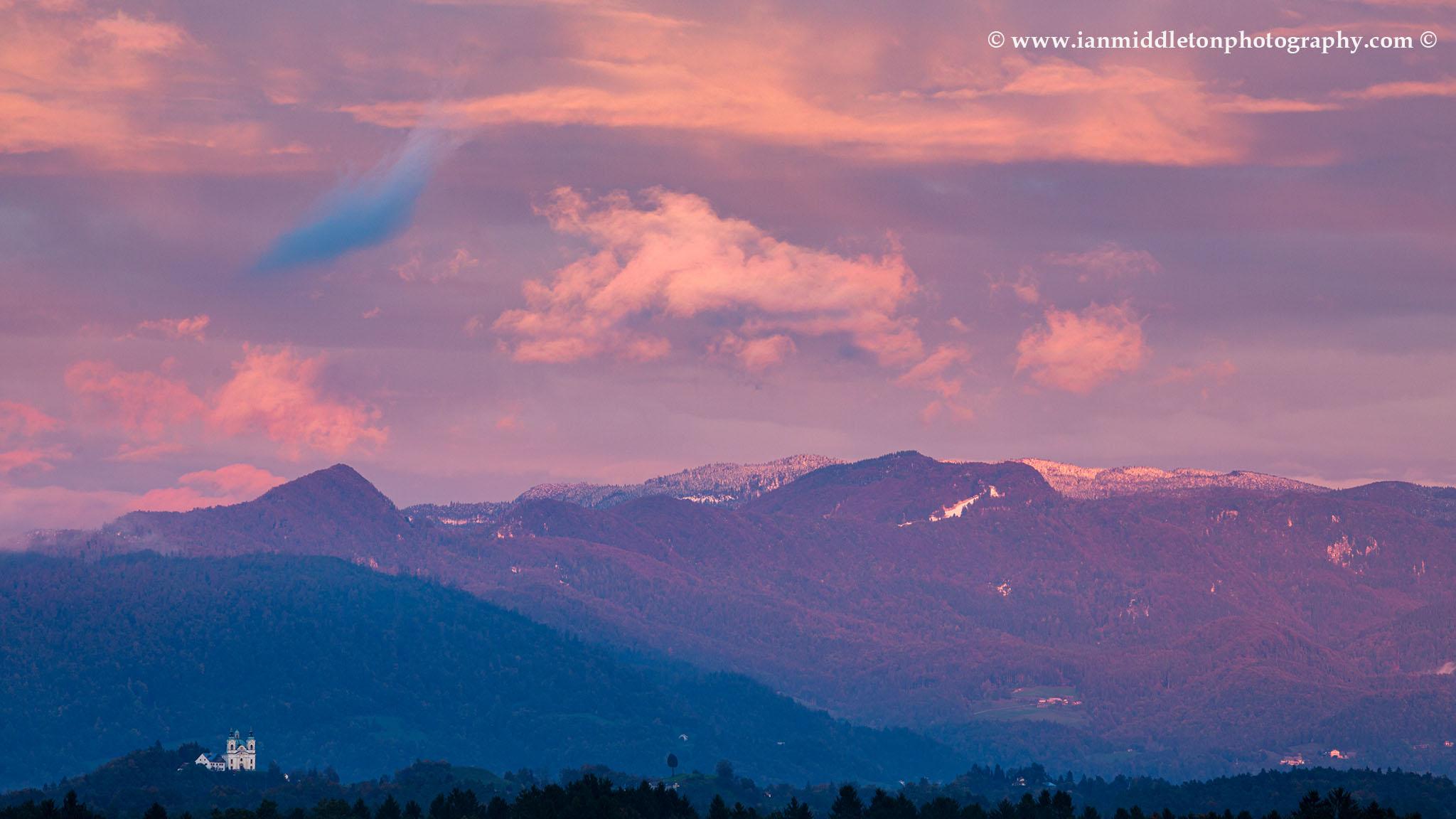 Sunset over Saint Ana church in Tunjice, Slovenia. Shot from a field in Brnik, near the Ljubljana airport.